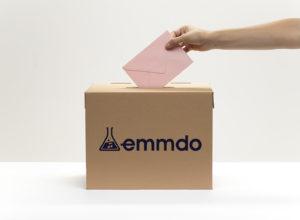 hand-puts-pink-envelope-into-vote-box